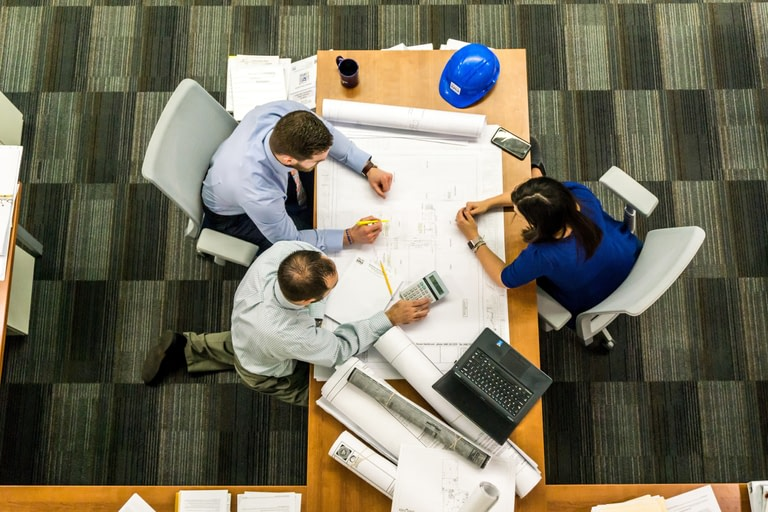 Construction workers round a table